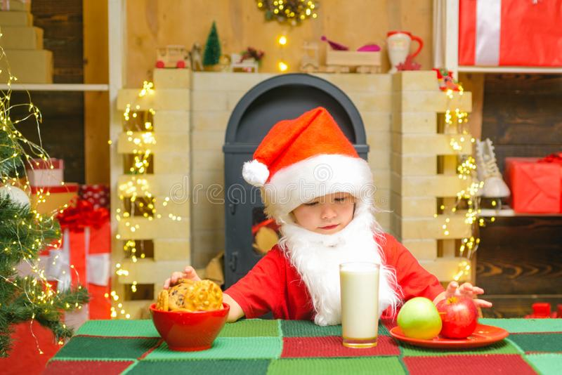 Cheerful Santa Claus holding glass with milk and cookie with fireplace and Christmas Tree in the background. Merry. Christmas stock images