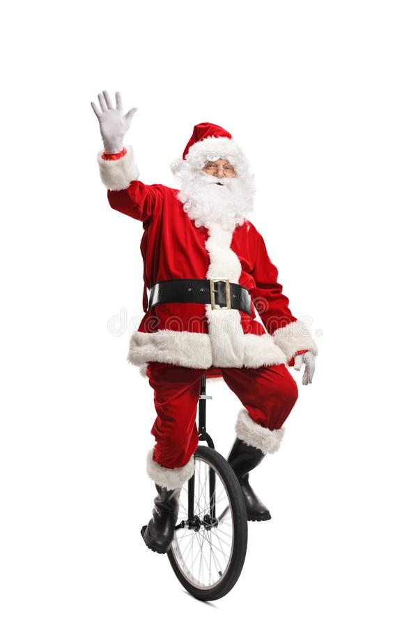 Cheerful santa claus riding a unicycle and waving at the camera. Full length portrait of a cheerful santa claus riding a unicycle and waving at the camera royalty free stock photos