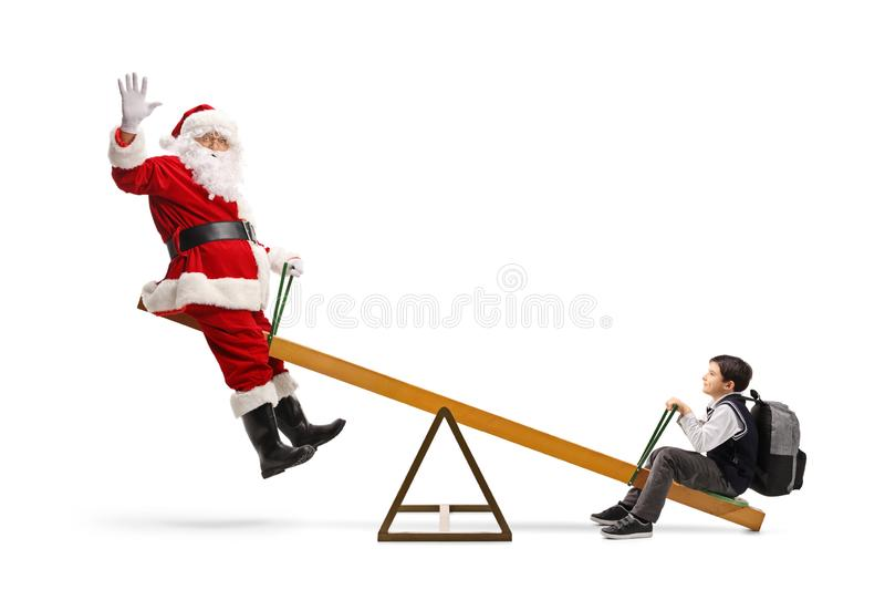 Cheerful Santa Claus waving and playing on a seesaw with a happy schoolboy stock image