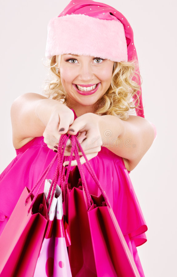 Cheerful santa helper girl with shopping bags stock photography