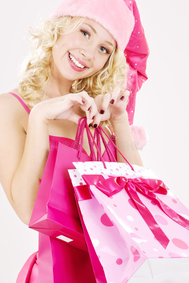 Cheerful santa helper girl with shopping bags stock photos