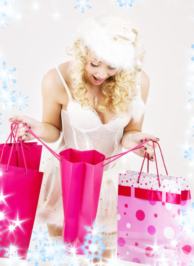 Cheerful santa helper girl with shopping bags. Picture of cheerful santa helper girl with shopping bags royalty free stock photo