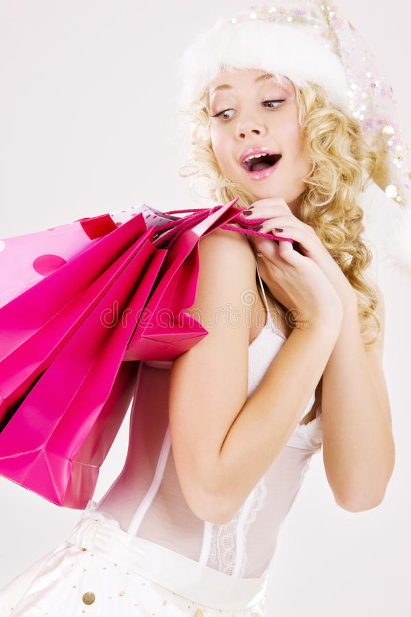 Cheerful santa helper girl with shopping bags royalty free stock photo