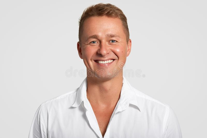 Cheerful satisfied male with positive expression, shows white teeth, being in good mood after successful meeting, dressed in white royalty free stock photos