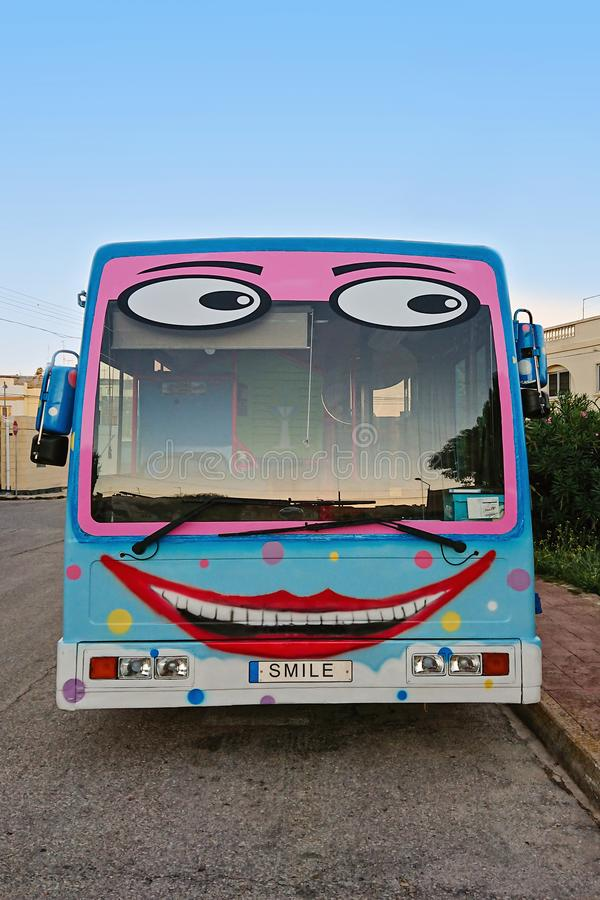 A cheerful school bus with painted funny face and a smile. Cheerful school bus with painted funny face and smile on street stock image