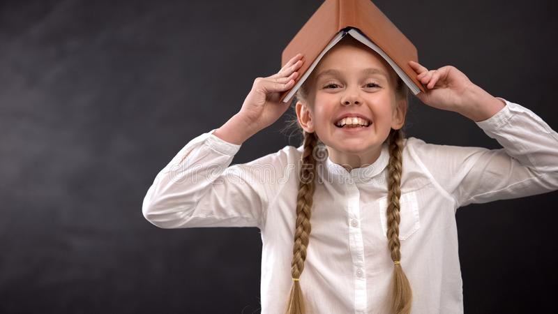 Cheerful schoolgirl with book on head laughing, having fun at school, fooling. Stock photo stock photos