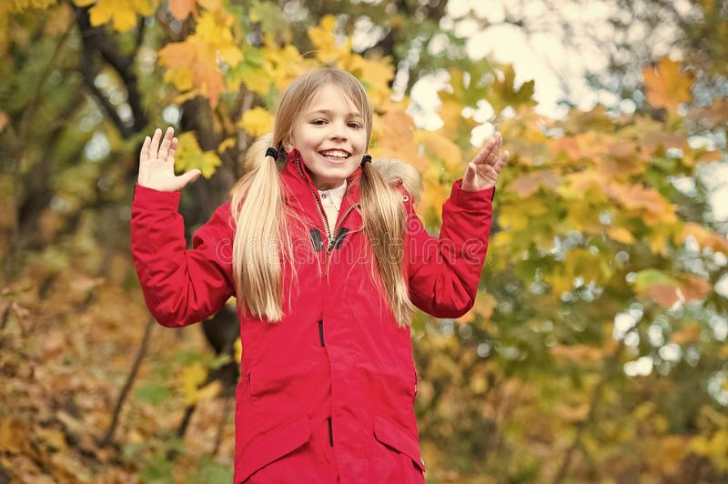 Cheerful schoolgirl. Child blonde long hair walking in warm jacket outdoor. Girl happy in red coat enjoy fall nature stock images