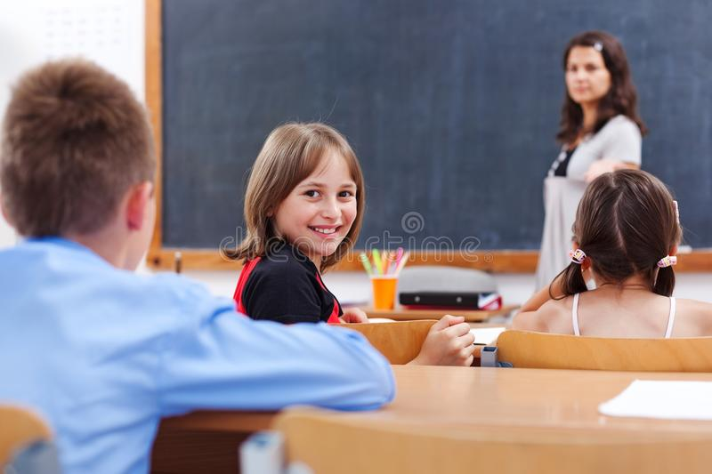 Cheerful schoolgirl in class room. Cheerful school girl looking back in class room while the teacher explains stock photography