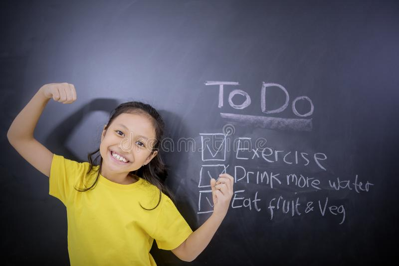 Cheerful schoolgirl standing with lists of to do stock photo
