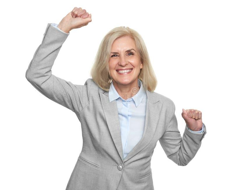 Cheerful senior business woman standing over white studio wall stock photo