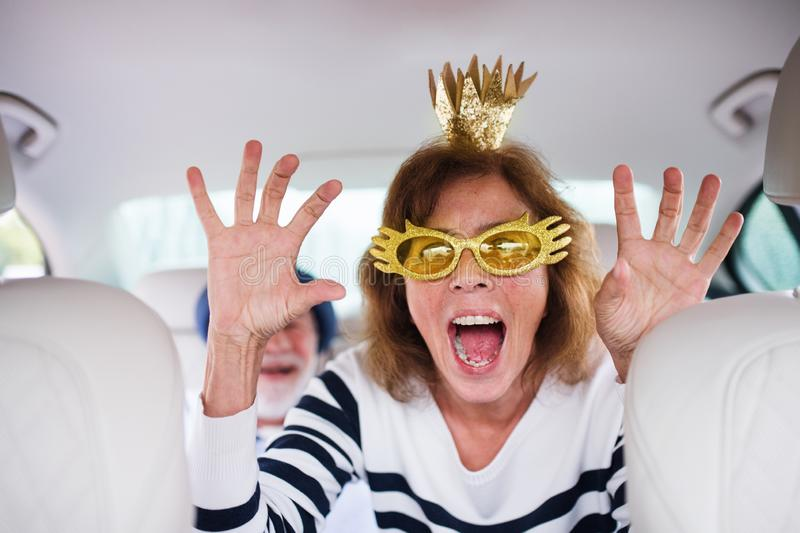 Cheerful senior couple with party accessories sitting in car, having fun. royalty free stock photos