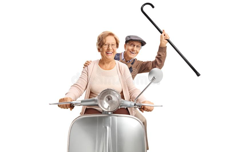 Cheerful senior couple riding a vintage scooter and holding a cane up. Isolated on white background stock photography