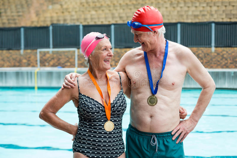 Cheerful senior couple standing at poolside stock images