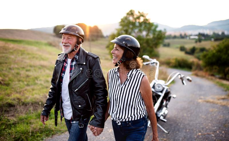 A cheerful senior couple travellers with motorbike in countryside. stock image