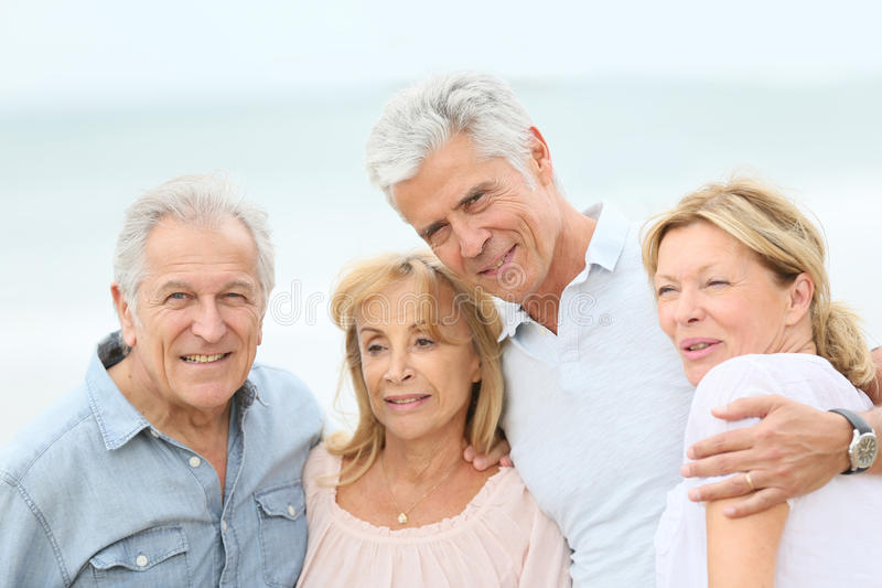 Cheerful senior couples walking on the beach. Group of senior people at the beach stock photography
