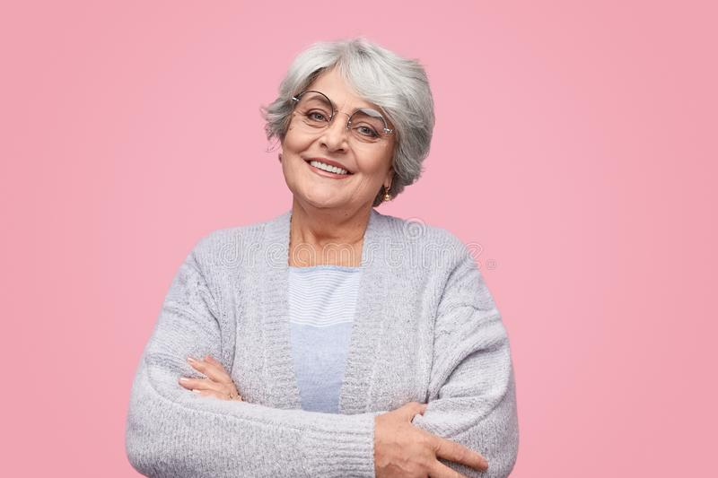 Cheerful senior female with crossed arms royalty free stock photos
