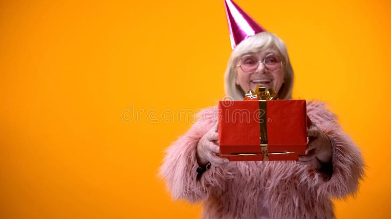 Cheerful senior female in funny clothing giving birthday gift, celebration royalty free stock photography