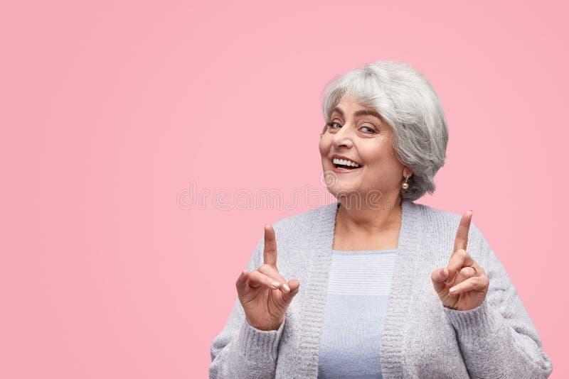Cheerful senior female pointing up stock photo