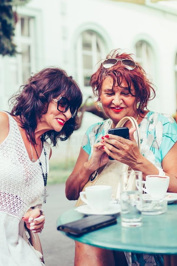 Cheerful senior ladies using a smart phone, laughing and talking while sitting outdoors. In a cafe royalty free stock images