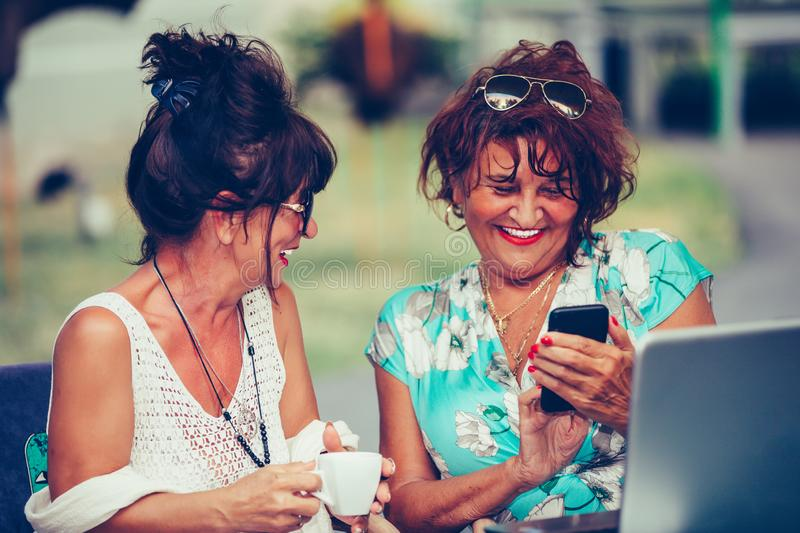 Cheerful senior ladies using a smart phone and talking while sitting outdoors. In a cafe stock image