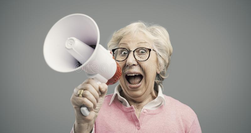 Cheerful senior lady shouting into a megaphone stock photo