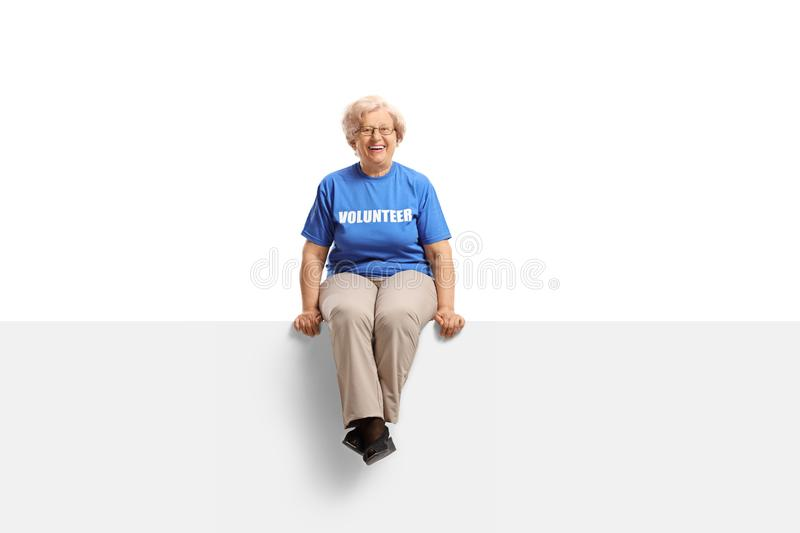 Cheerful senior lady volunteer sitting on blank white banner. Isolated on white background royalty free stock photography