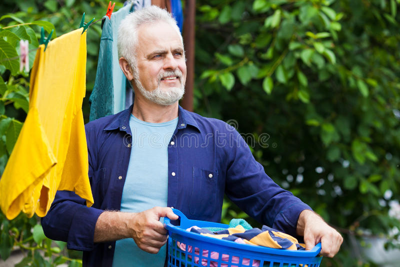 Cheerful senior man with laundry basket outdoor stock photography