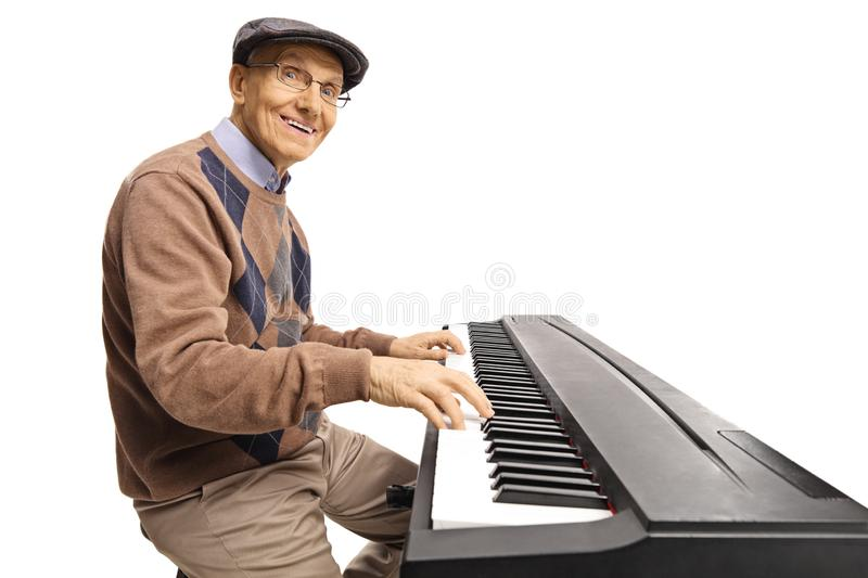 Cheerful senior man playing a digital keyboard piano royalty free stock image
