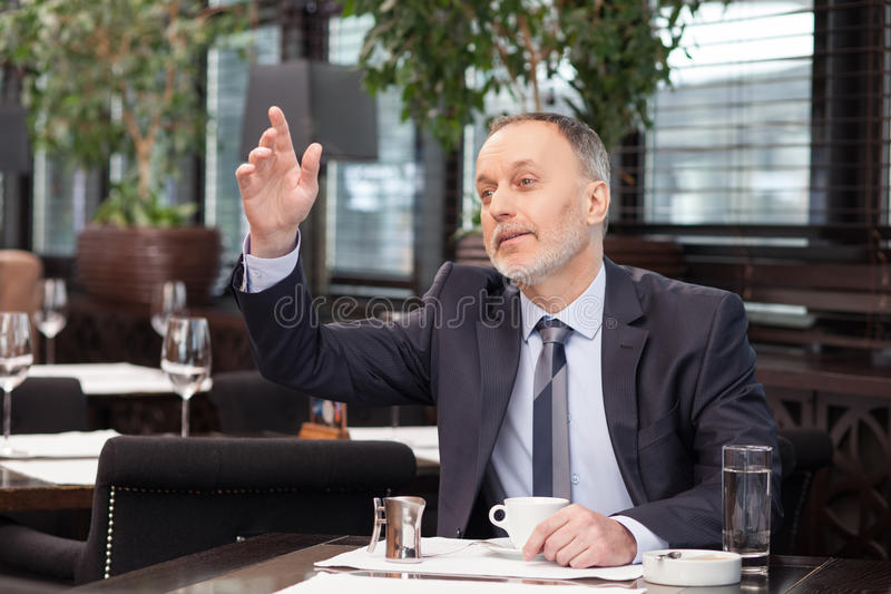 Cheerful senior man is resting in restaurant royalty free stock photo