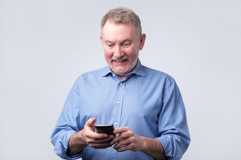 Cheerful senior man texting with friend or his family smiling. royalty free stock photos