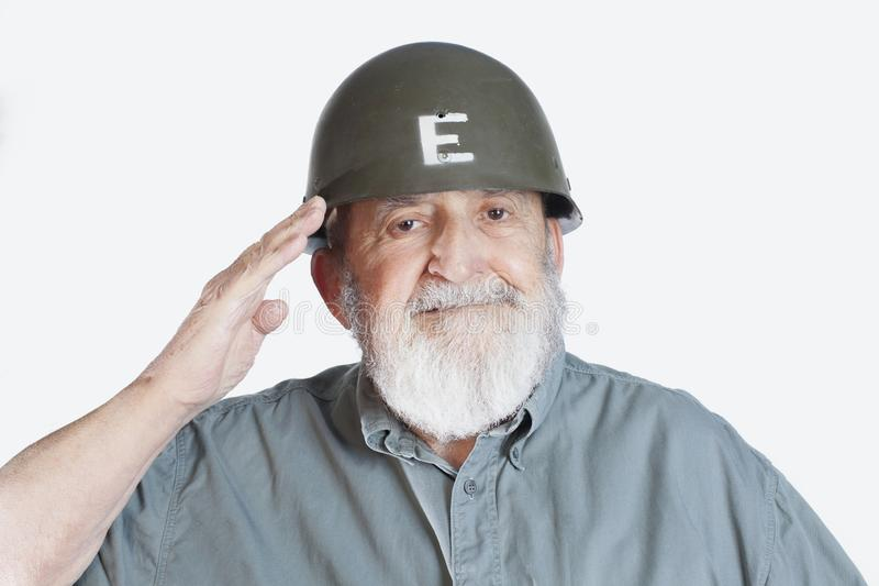 Cheerful senior soldier veteran saluting isolated on white background. Smiling happy elderly soldier veteran saluting stock photos