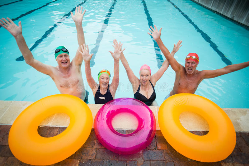 Cheerful senior swimmers with inflatable rings at poolside stock image