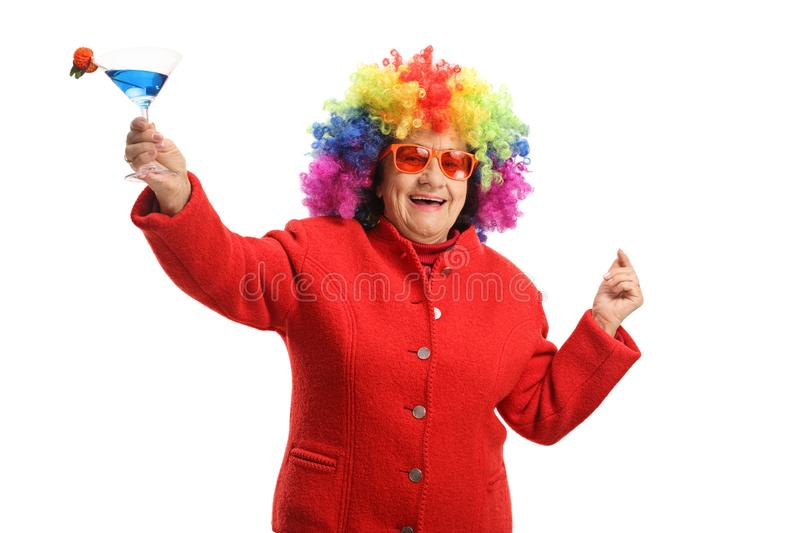 Cheerful senior woman with a colorful wig and a cocktail. Isolated on white background stock image