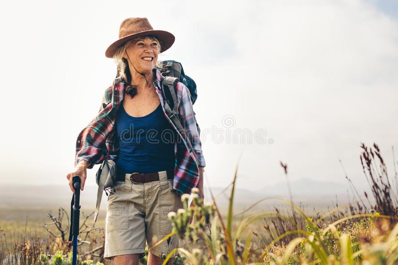 Cheerful senior woman enjoying her hiking trip royalty free stock images