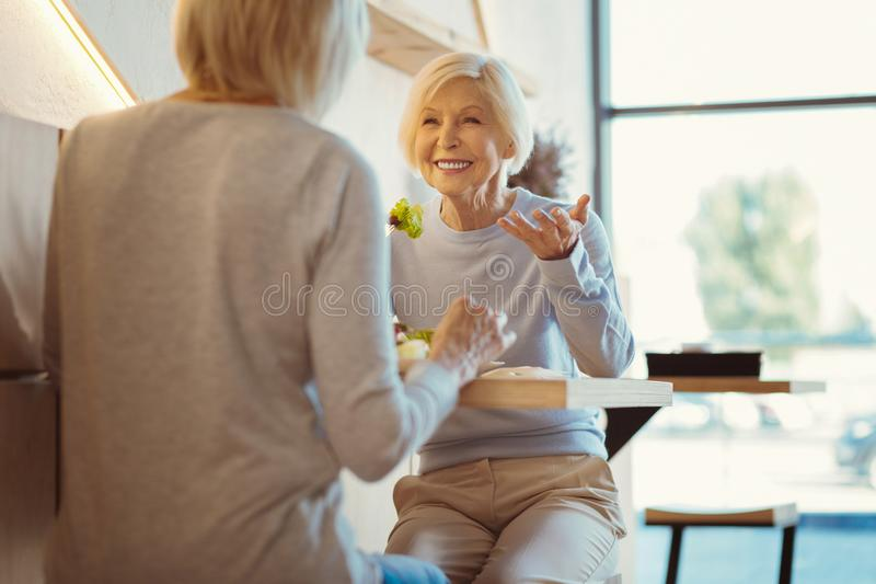 Cheerful senior woman enjoying her meeting. Pleasurable time. Cheerful nice senior women smiling and looking at her friend while enjoying their meeting royalty free stock images