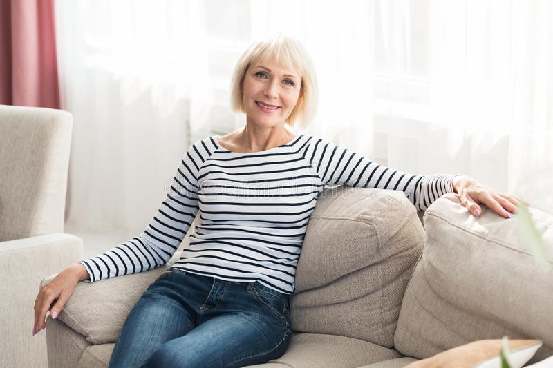 Cheerful senior woman feeling happy and relaxed, sitting on couch royalty free stock photos