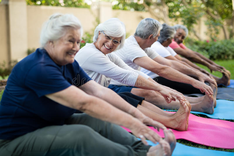 Cheerful senior woman with friends doing stretching exercise. Cheerful senior women with friends doing stretching exercise at park stock images