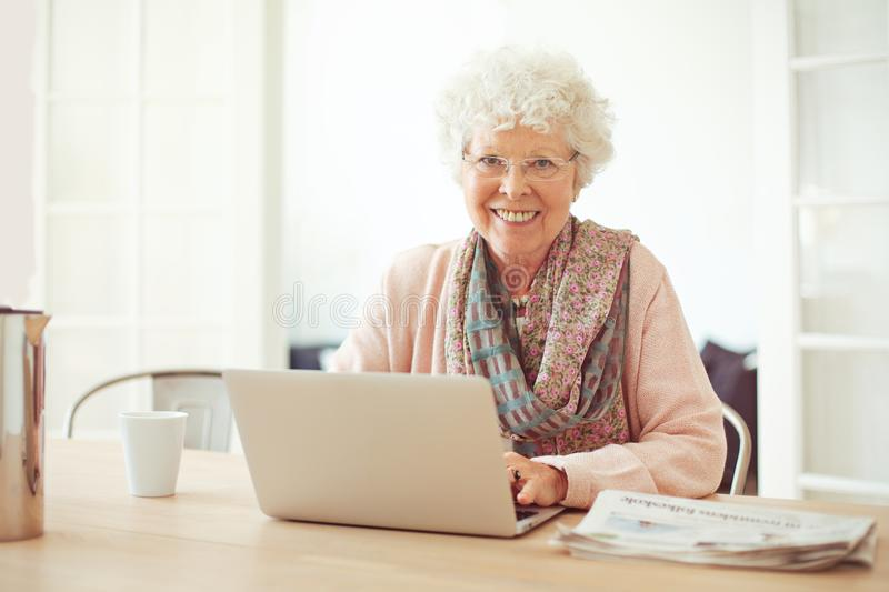 Cheerful Senior Woman at Home with Laptop royalty free stock photography