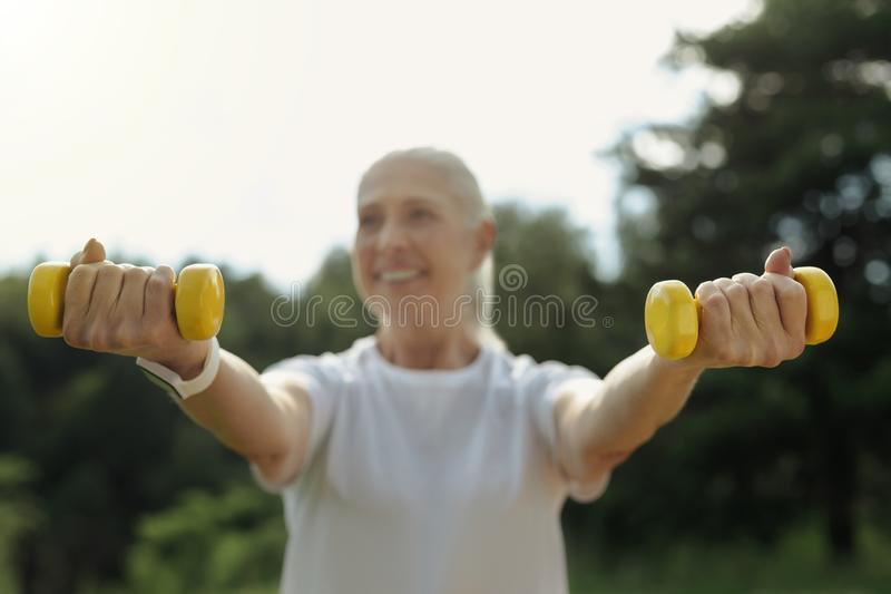 Cheerful senior woman lifting dumbbells outdoors royalty free stock image