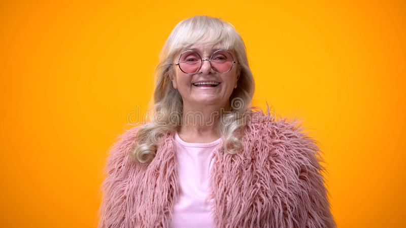 Cheerful senior woman in pink coat and round sunglasses smiling on camera stock image