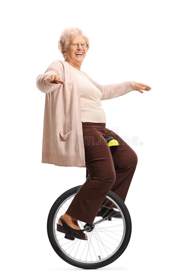 Cheerful senior woman riding a unicycle and balancing with hands. Full length shot of a cheerful senior woman riding a unicycle and balancing with hands isolated royalty free stock image