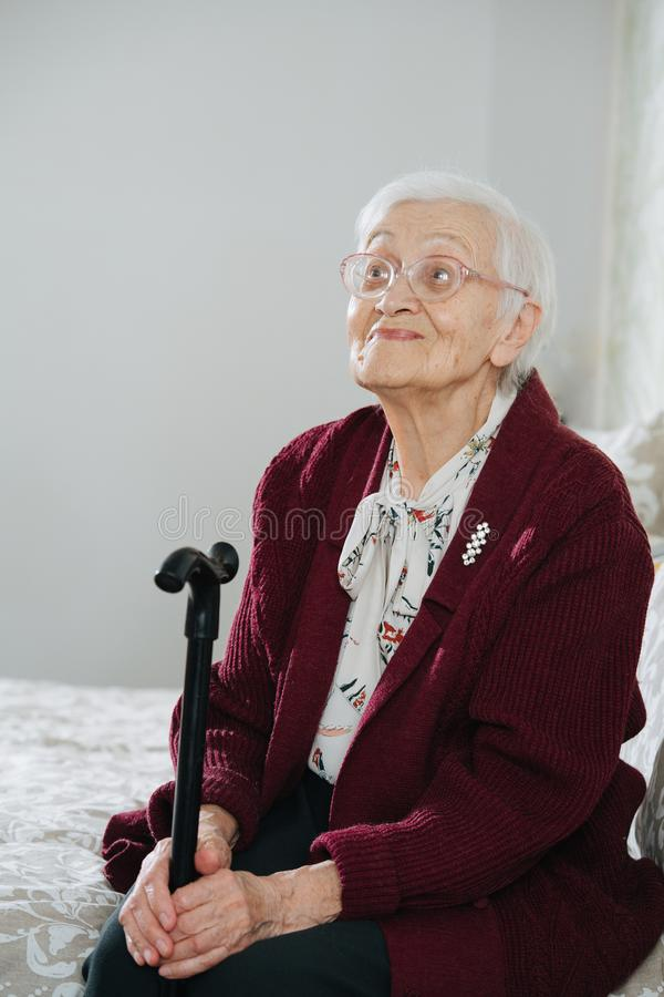Cheerful senior woman sitting on bed with walking stick at home stock photo
