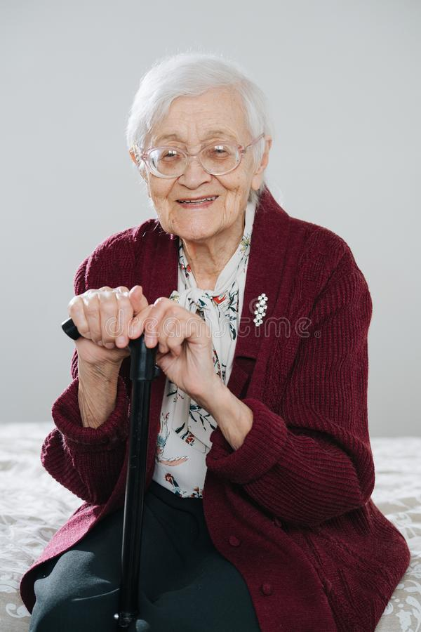 Cheerful senior woman sitting on bed with walking stick at home stock photography