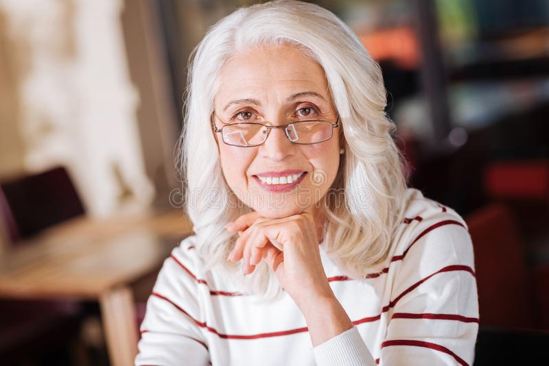 Cheerful senior woman sitting and smiling peacefully stock image