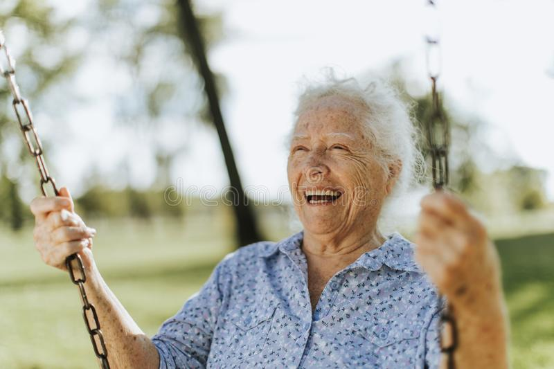 Cheerful senior woman on a swing at a playground royalty free stock photo