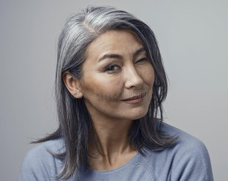 Charming Asian mature woman smiles at camera royalty free stock image