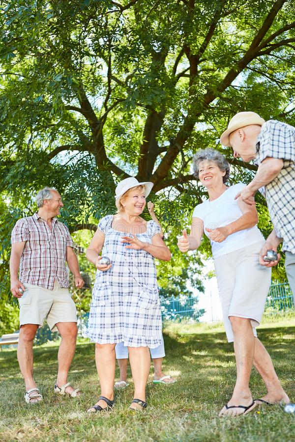 Cheerful seniors group playing boules. Together in the summer at the retirement home royalty free stock image