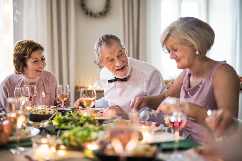 Seniors sitting at the table on a indoor family birthday party, eating. royalty free stock image