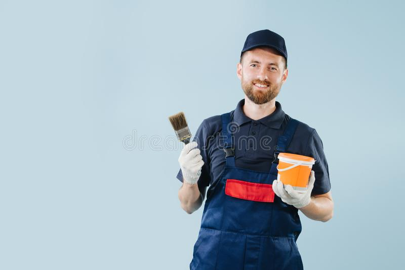 Cheerful service worker with paint can and brush in hands dressed in uniform. Cheerful service worker with paint can and wide brush in hands. He is dressed in royalty free stock photo