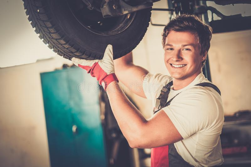 Cheerful serviceman in a car workshop. Cheerful serviceman checking suspension in a car workshop royalty free stock photo